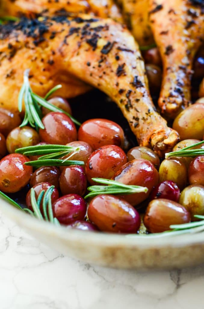 Roasted chicken with rosemary and grapes in a roasting pan