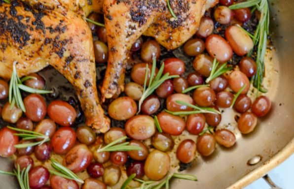 An overhead image of a roasted chicken with rosemary and grapes in a roasting pan