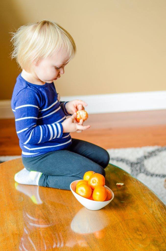 A toddler peeling cuties mandarin oranges on a table