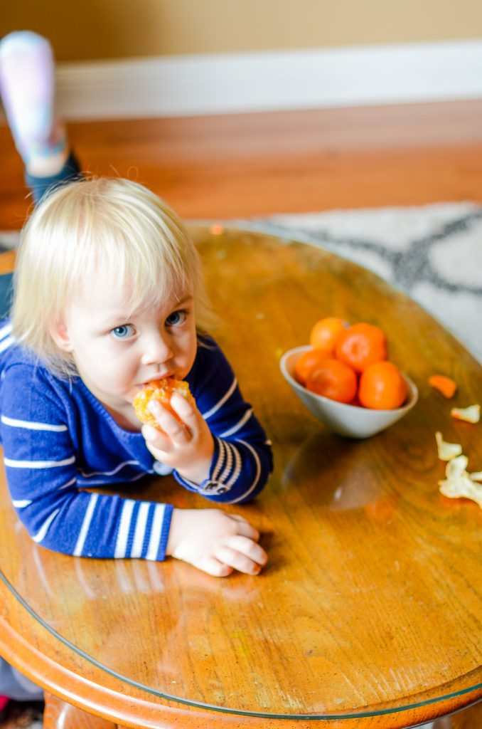 A toddler eating a Cuties mandarin orange next to a bowl of them.