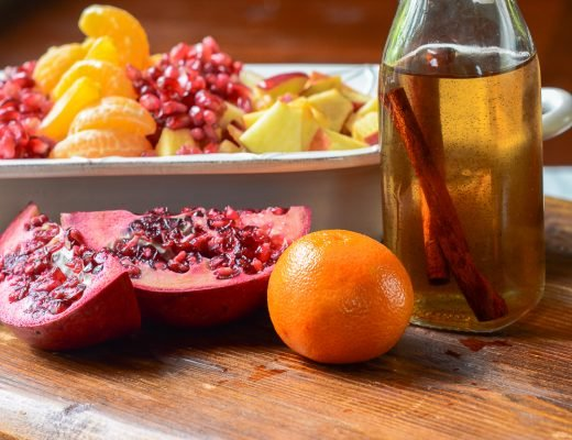 A bowl of fruit salad next to a pomegranate, mandarin orange, and syrup on a wooden cutting board