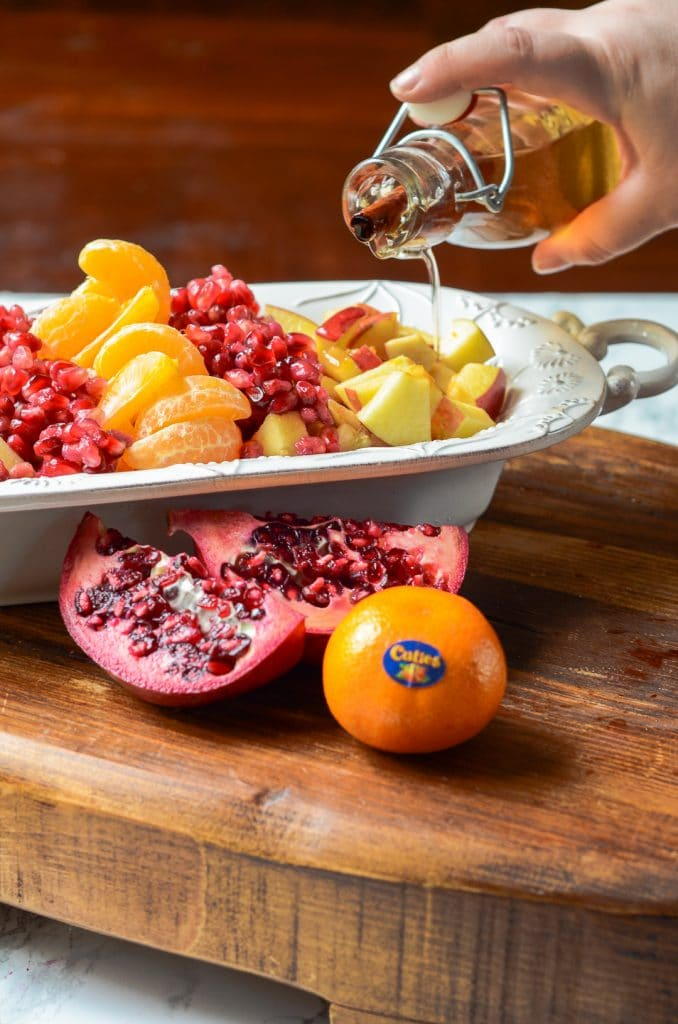 Syrup being poured onto fruit next to a cut pomegranate and cuties mandarin orange.
