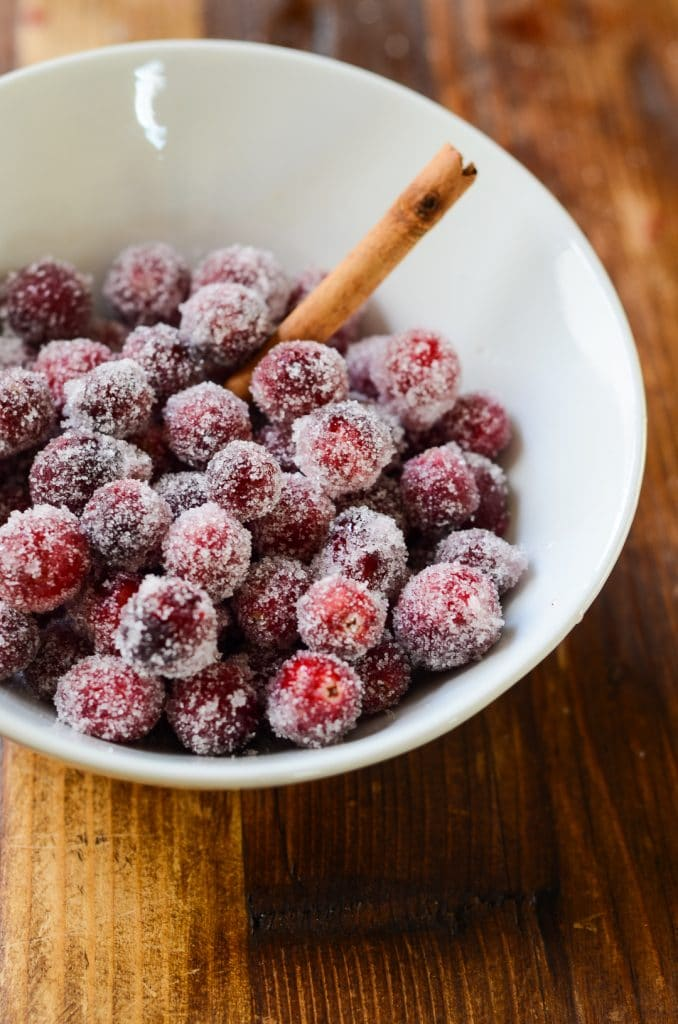 A bowl of sugared cranberries with a cinnamon stick.