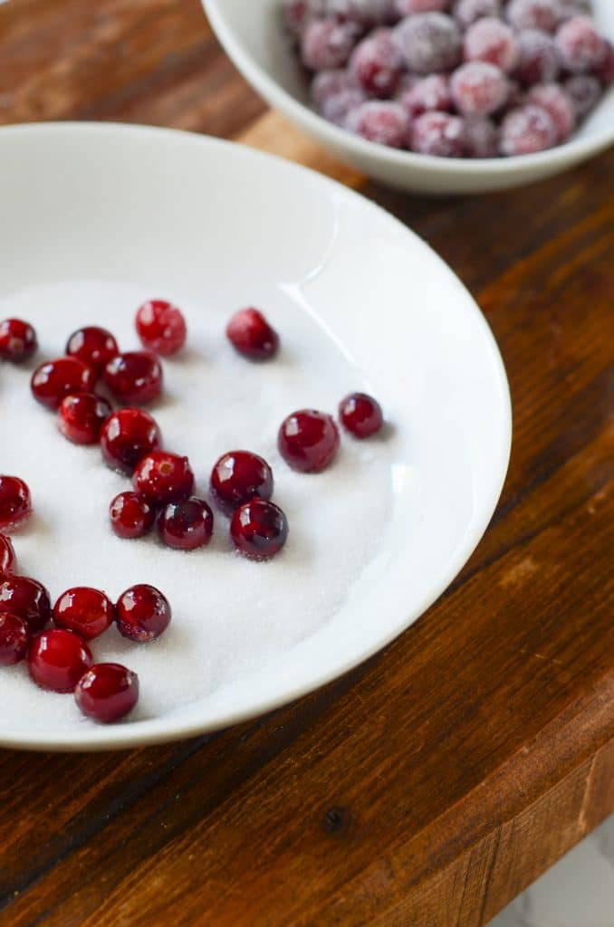 Cranberries getting ready to be stirred in sugar on a white plate.