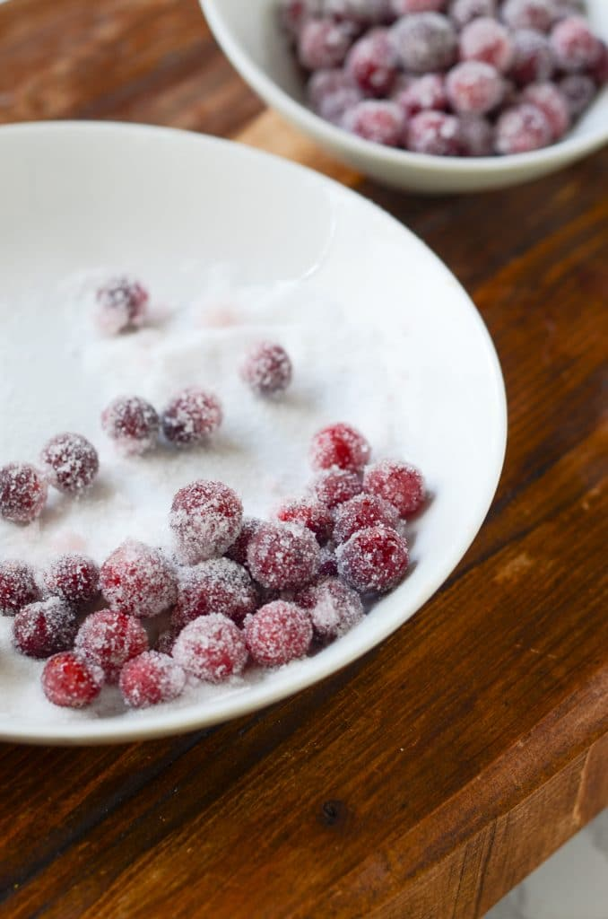 Cranberries being rolled in sugar on a white plate