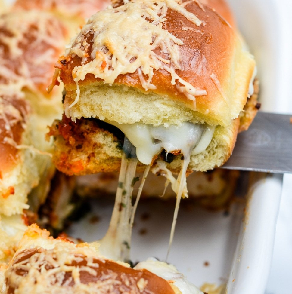 a pesto chicken parmesan slider being removed from the pan with a spatula
