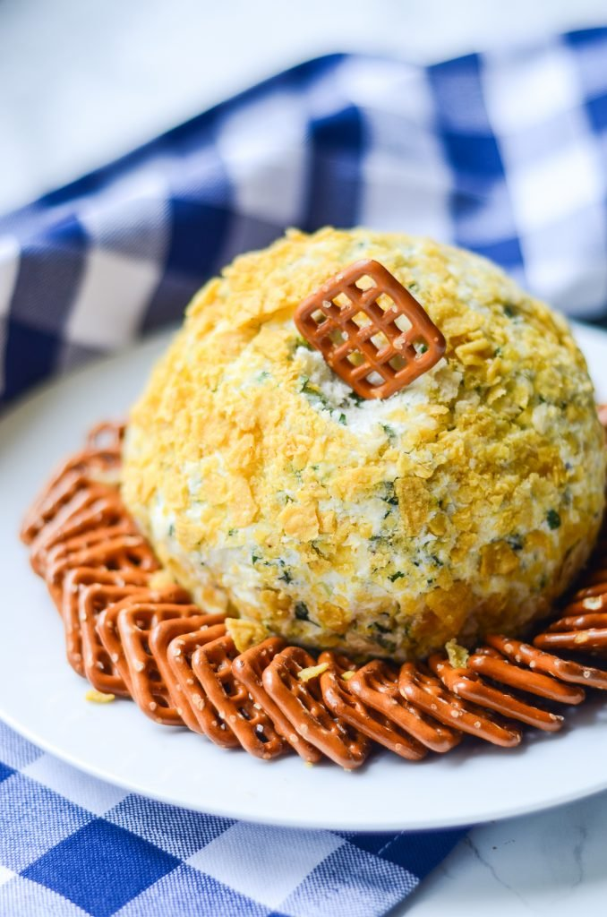 a square pretzel tucked into a Fire Roasted Jalapeno Cheese Ball surrounded by pretzels