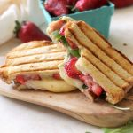 Two halves of a panini on cutting board by basket of strawberries