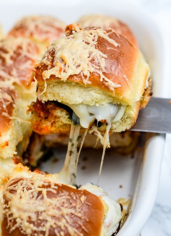 a single Pesto Chicken Parmesan Slider being pulled from the pan with cheese stringing from it