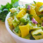 white bowl of mango avocado salsa next to fresh cilantro