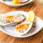 Two halved oysters on a w white plate with lemon wedge
