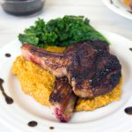 Lamb chops on polenta next to greens on a white plate
