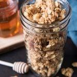 A mason jar of granola next to jar of honey and honey dipper