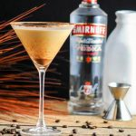 coffee cocktail in a martini glass with bottle of smirnoff and jigger behind it