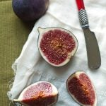 Cut figs on a white napkin next to cheese knife