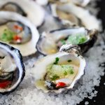 Seven halved Oysters with Granita on tops of rock salt