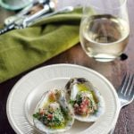 Two oysters on a white plate next to green napkin and white wine