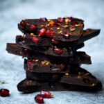 a stack of broken pieces of winter raw chocolate bar next to pomegranate arils