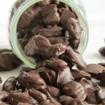 a mason jar spilling out chocolate covered almonds
