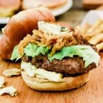 Roasted Garlic Burger with Cambozola on a wooden cutting board next to french fries
