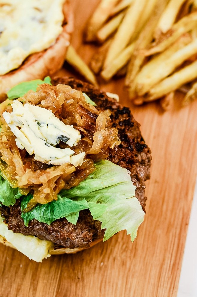 roasted garlic burger on a cutting board next to french fries