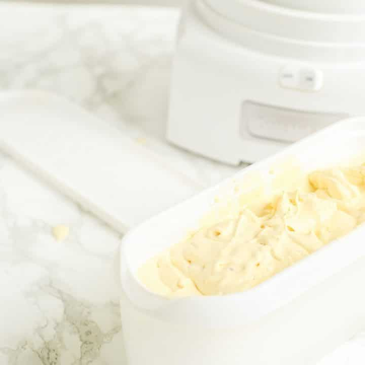 a white tub of homemade custard ice cream in front of an ice cream maker