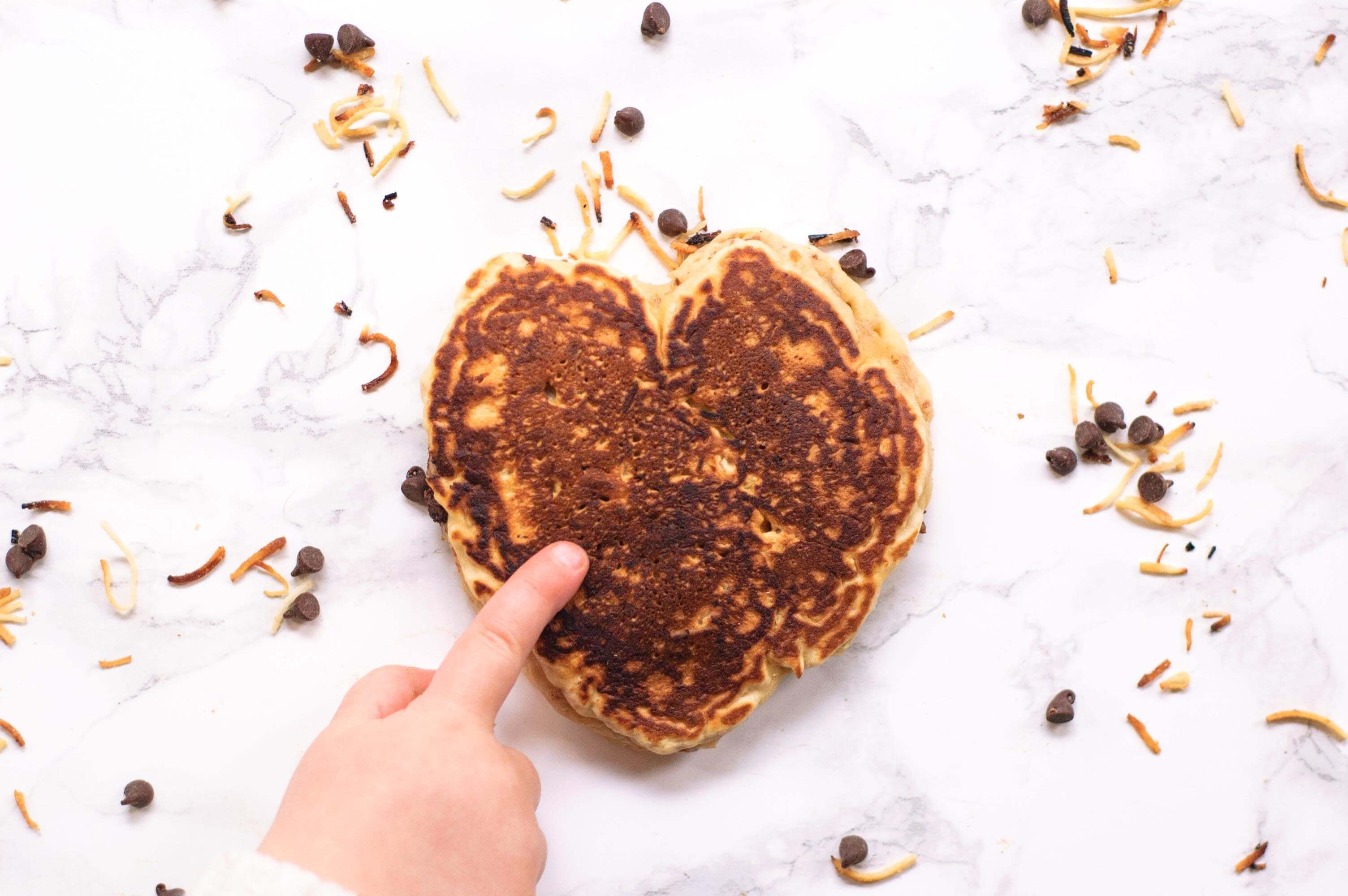 child's finger pointing to a heart shaped chocolate chip pancake