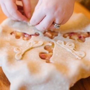 two hands placing pie crust decorations on a pie