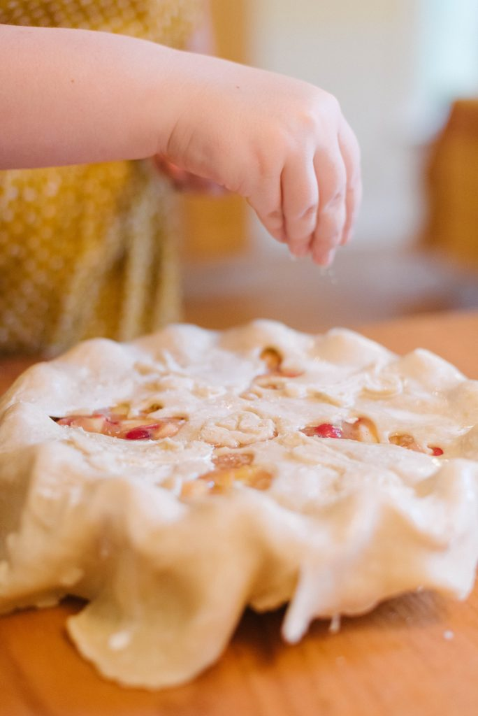 Turbinado sugar being sprinkled onto a completed pie. How To Make Pie Crust