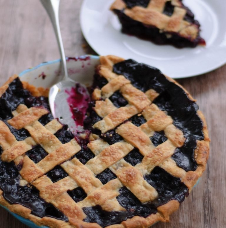 Spiced blueberry pie with a slice cut out next to a plate with the slice on it.