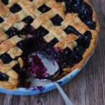 A pie server sitting in the opening of a missing piece of spiced blueberry pie.