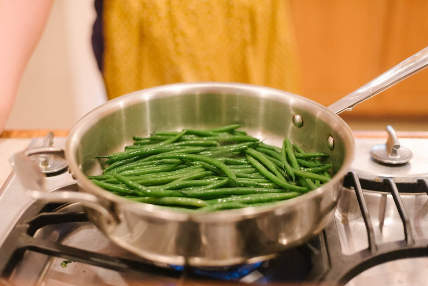 A saute pan of fresh haricots verts being cooked.