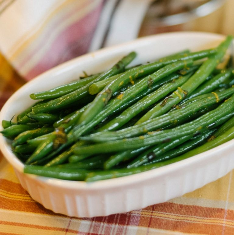 a small bowl of haricots verts on an autumnal colored tablecloth