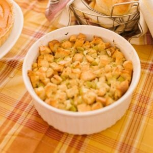 A white bowl of brown butter cornbread dressing on an autumnal tablecloth