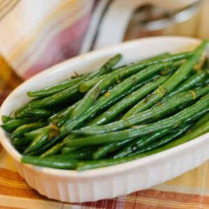 A small serving dish of haricots verts on an autumnal tablecloth.
