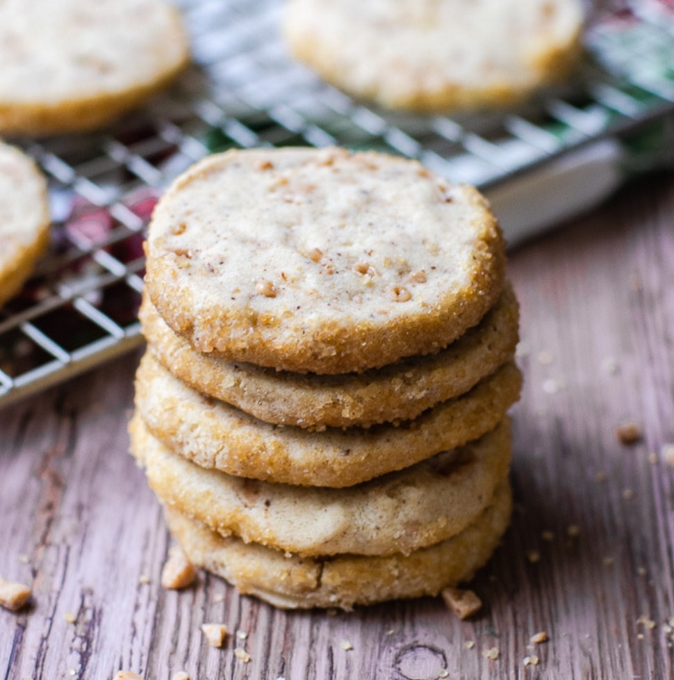 five shortbread cookies stacked in front of a cooling rack