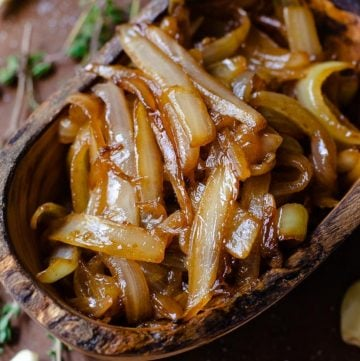 overhead image of a wooden bowl of caramelized onion at an angle