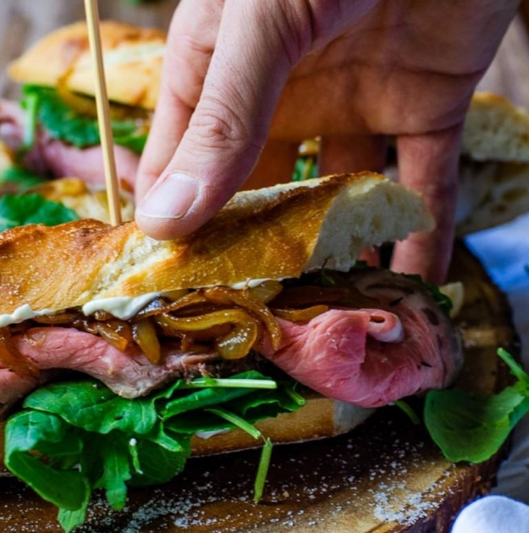 a hand grabbing a prime rib sandwich off of a wooden board