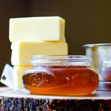 small mason jar of brown butter with three sticks of regular butter stacked behind it