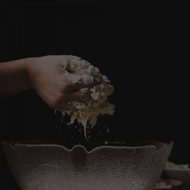 Black overlay on hands pulling dough out of a bowl.