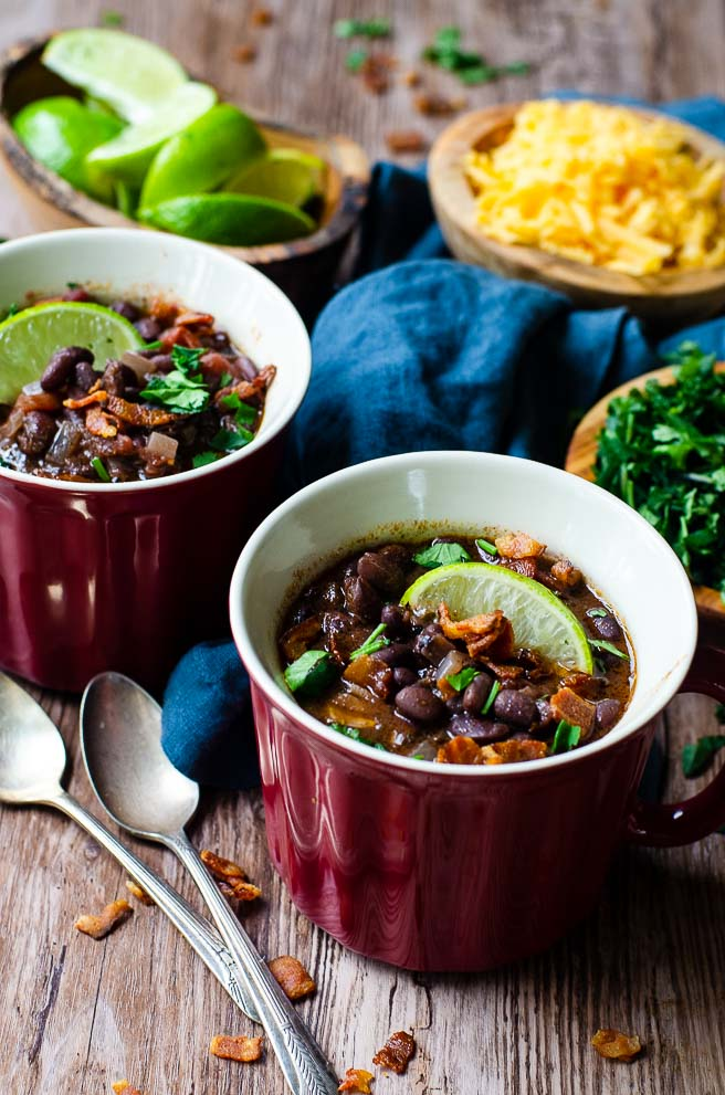 Two red bowls of black bean soup next to bowls of toppings and two spoons