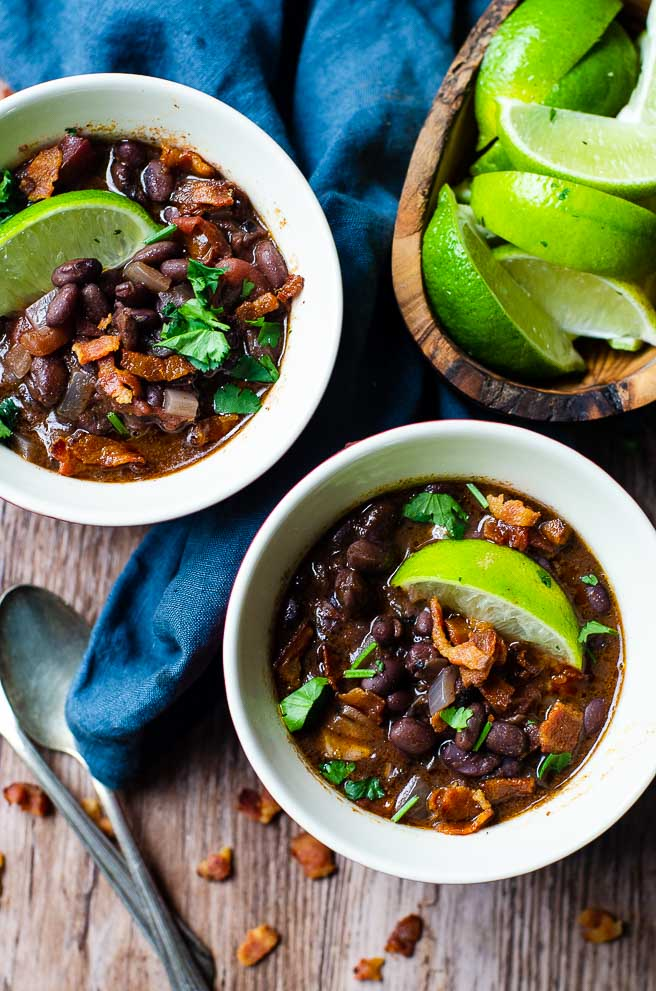 An overhead image of two bowls of black bean soup next to a wooden bowl of limes