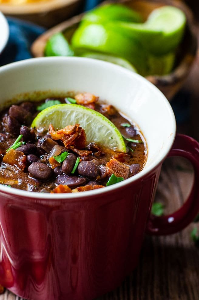 Close up of black bean soup garnished with a lime in a red bowl