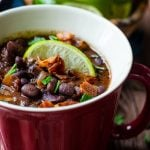 A lime wedge and crispy bacon garnish a red mug of black bean and bacon soup.