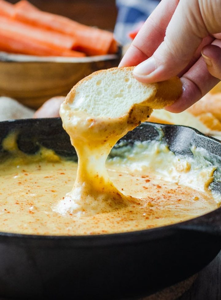 A piece of bread being dipped into smoky beer cheese dip in a cast iron pan