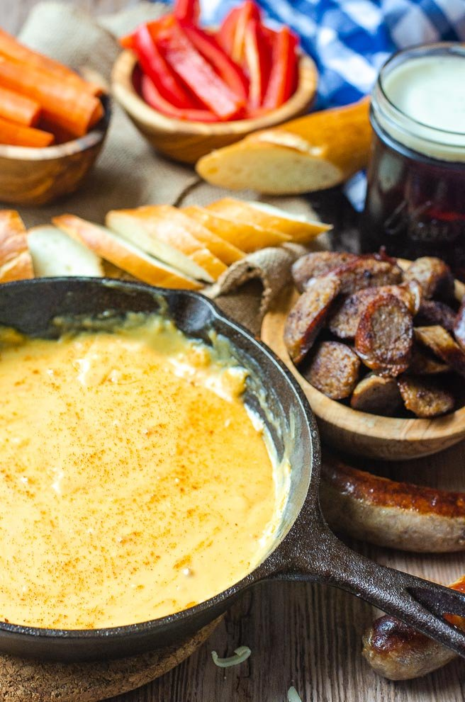 Cast iron pan of beer cheese dip surrounded by bowls of things to dip in it