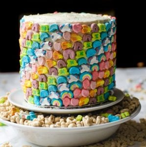 A lucky charms cake sitting on a pedestal inside a bowl of lucky charms.