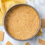 Overhead of a springform pan with a graham cracker crust. Broken graham crackers surround it.
