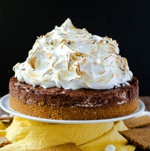 A s'mores pie piled very high with toasted marshmallow fluff.