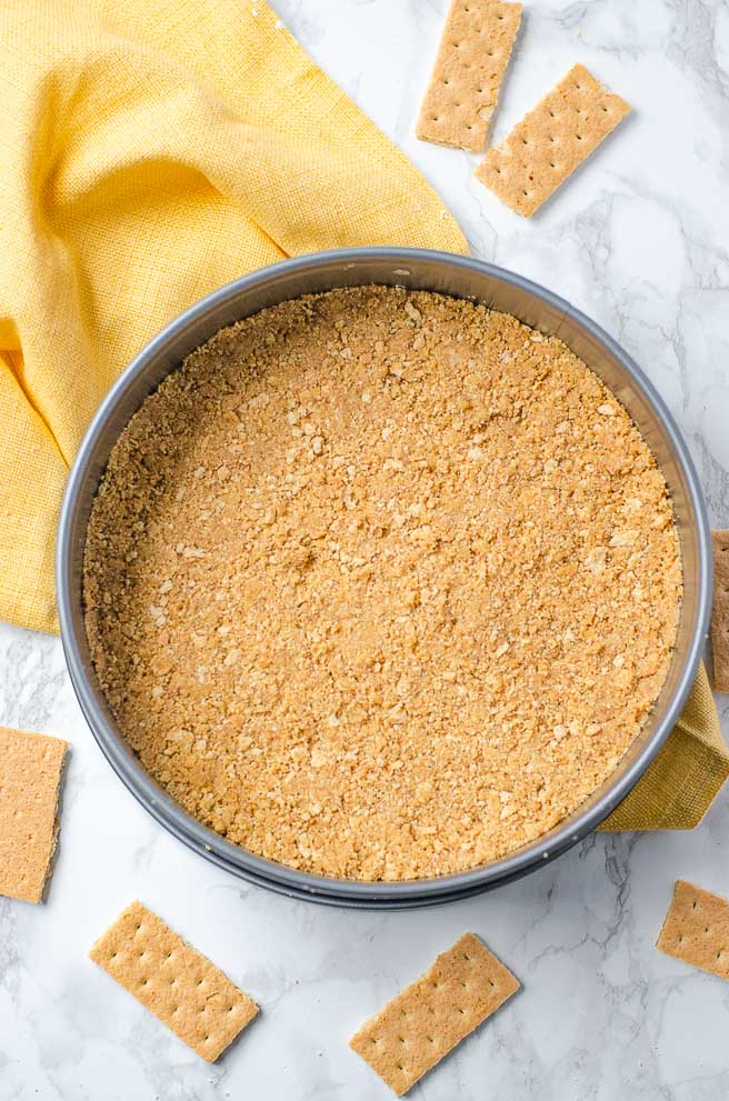 overhead shot of graham cracker crust in a springform pan. It is on top of a yellow napkin and surrounded by graham crackers.